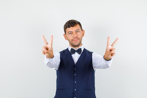 Kelner pokazuje znak v w koszuli, kamizelce i wygląda wesoło. przedni widok.