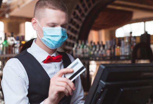 Kelner pracuje w restauracji w masce medycznej.