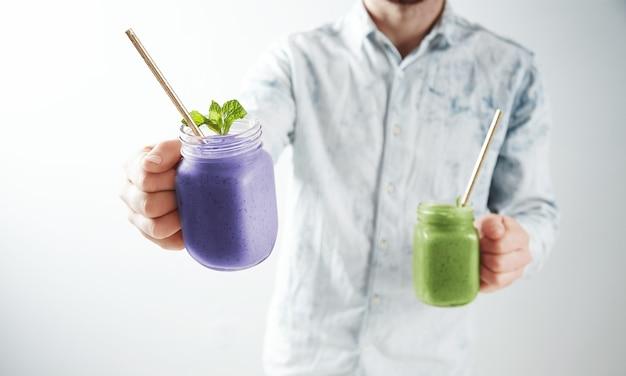 Kelner proponuje dwa smaczne zimne smoothie z jagód i kiwi w rustykalnych słoiczkach ze słomką w środku