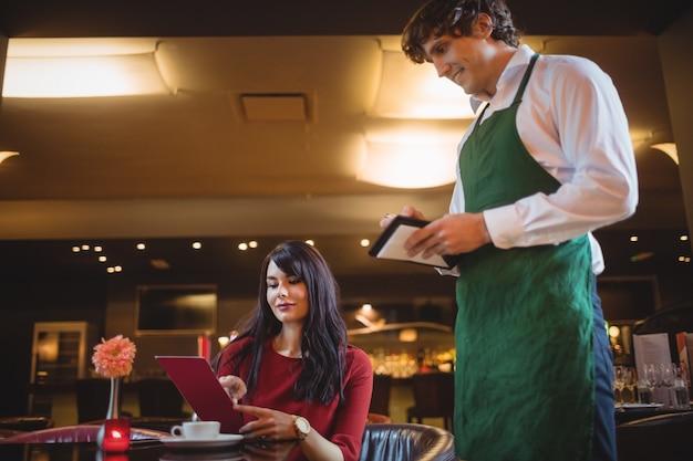 Kelner przyjmuje zamówienia od kobiety