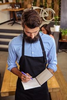 Kelner przyjmuje zamówienie w swojej książce