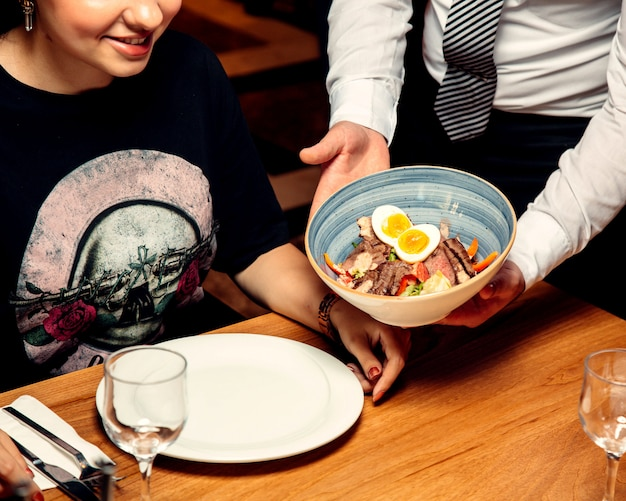 Kelner przynosi kobiecie miskę sałatki mięsnej