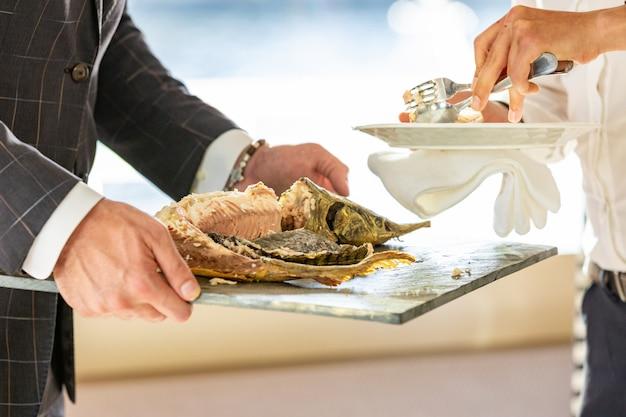 Kelner rozdrabnia pieczonego jesiotra w restauracji