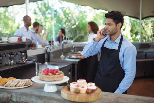 Kelner rozmawia przez telefon komórkowy
