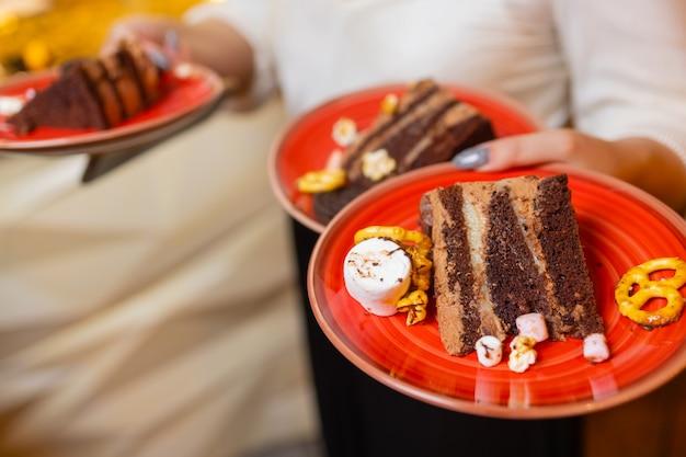 Kelner serwujący dwa kawałki ciasta na talerzach. w jednej ręce trzyma dwa talerze.