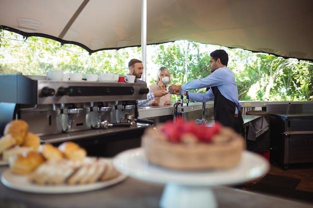 Kelner serwujący kawę klientowi przy ladzie