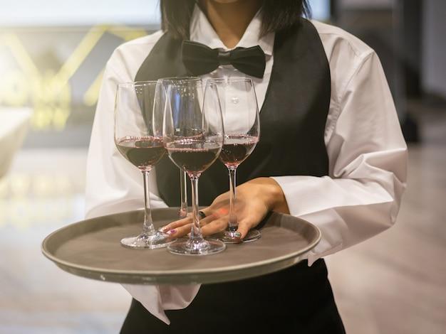 Kelner serwujący kieliszki czerwonego wina
