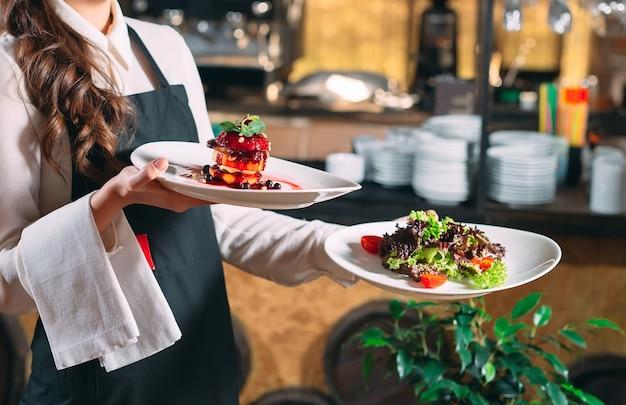 Kelner służący w ruchu na służbie w restauracji. kelner niesie naczynia.