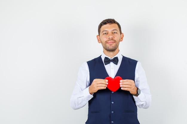 Kelner trzyma czerwone serce w koszuli, kamizelce i wygląda wesoło. przedni widok.