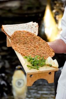 Kelner trzyma drewniany stojak z tureckim lahmajun do pizzy z cytryną i natką pietruszki