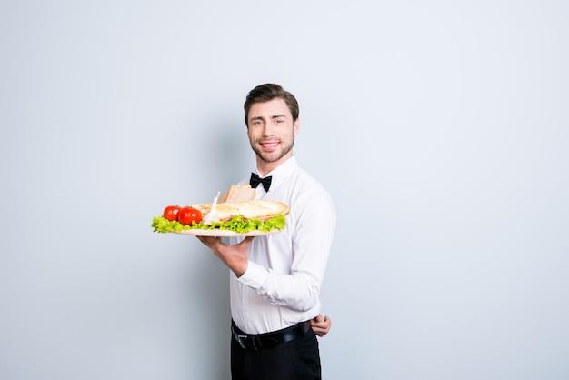 Kelner trzyma dużą tacę z przystawką