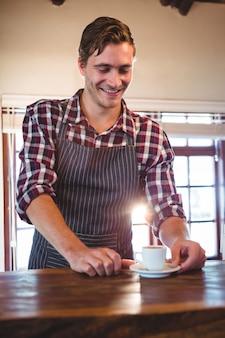 Kelner trzyma espresso