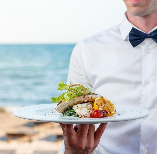 Kelner trzyma grillowaną rybę z cytryną, pomidorem, kremowymi ziołami w nadmorskiej restauracji