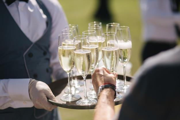 Kelner trzyma kieliszki do szampana na tace na zewnątrz