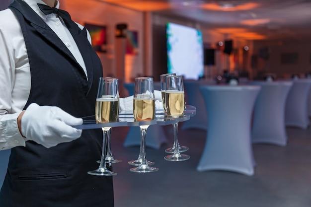 Kelner trzyma kieliszki z szampanem na tacy