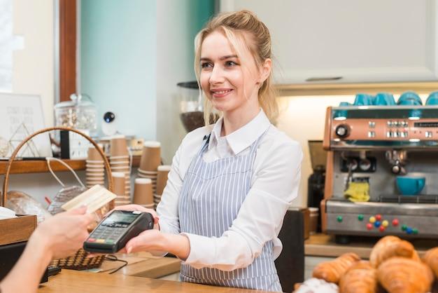 Kelner trzyma kredytową kartę zamachu maszynę podczas gdy klient pokazuje kredytową kartę w sklep z kawą