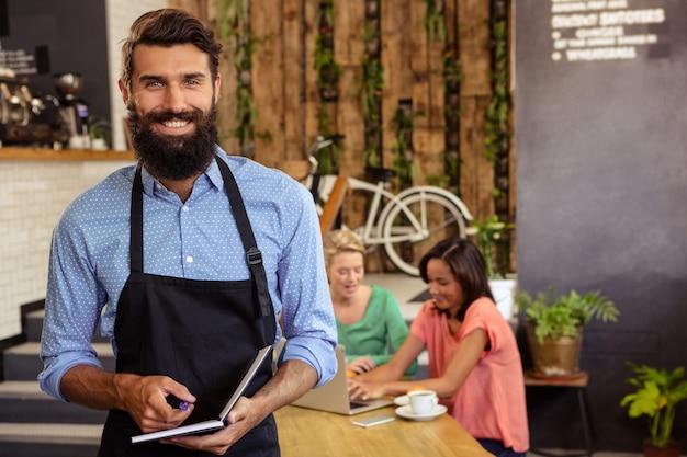 Kelner trzyma książkę i długopis
