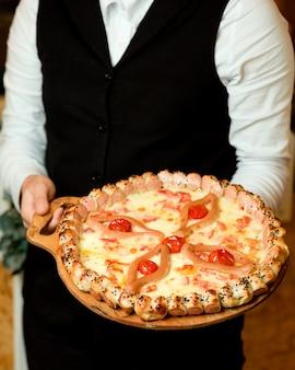 Kelner trzyma pizzę z kiełbasą z serem pomidorowym i plasterkami kiełbasy