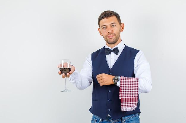 Kelner trzyma szklankę napoju w koszuli, kamizelce, dżinsach i wygląda pewnie. przedni widok.