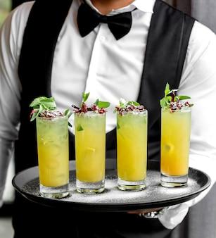 Kelner trzyma tacę z cytrynowymi szklankami mojito przyozdobionymi miętą i suszonymi różami