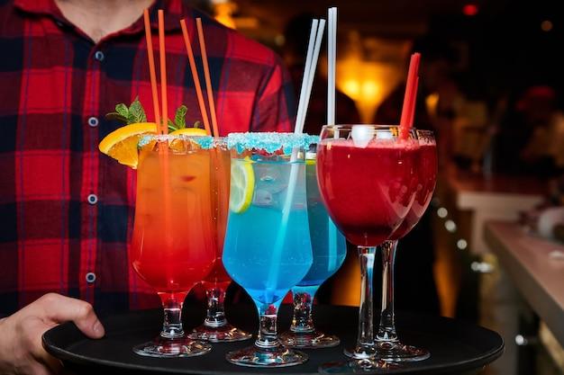 Kelner trzyma tacę z wielokolorowymi koktajlami alkoholowymi i bezalkoholowymi z lodem i słomkami