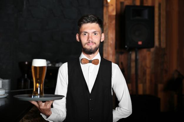 Kelner trzyma tacę ze szklanką piwa w pobliżu drewnianego baru