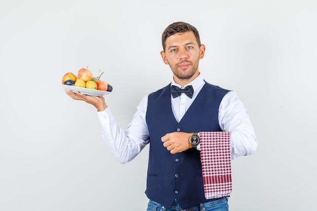 Kelner trzyma talerz pełen owoców w koszuli, kamizelce, dżinsach, widok z przodu.