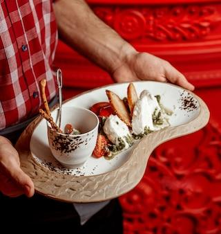 Kelner trzyma talerz sałatki pomidorowo-serowej z sosem pesto