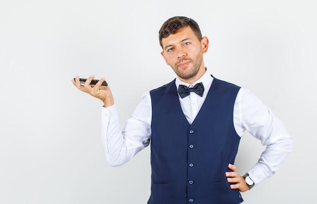 Kelner trzyma telefon komórkowy w koszuli, kamizelce i wygląda pewnie, widok z przodu.