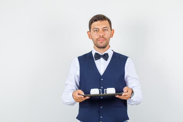 Kelner trzymający kubki na tacy w koszuli, kamizelce, muszce i wyglądający poważnie. przedni widok.