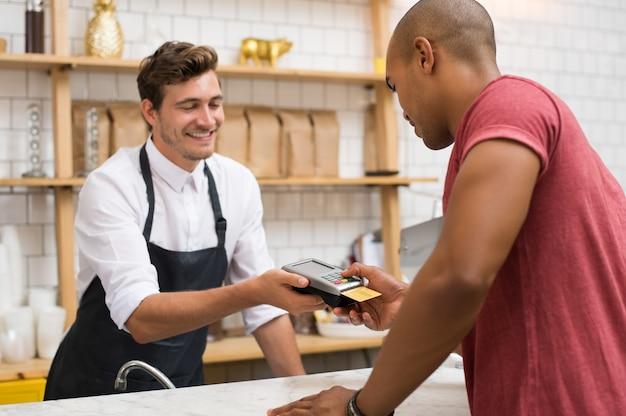 Kelner trzymający maszynę do przeciągania kart kredytowych podczas wpisywania kodu przez klienta