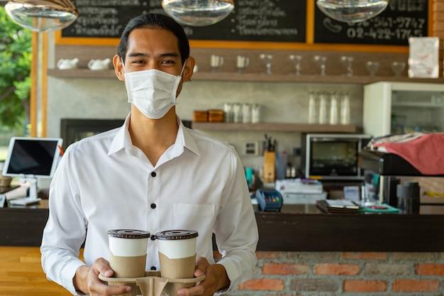 Kelner trzymający papierowe kubki z kawą i uśmiechnięty w masce chirurgicznej