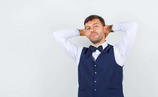 Kelner trzymający ręce za głową w koszuli, kamizelce i wyglądający pewnie, widok z przodu.
