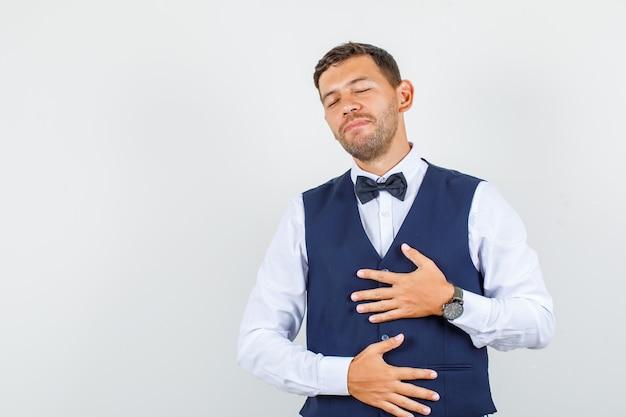 Kelner trzymający się za ręce na piersi i brzuchu w koszuli, kamizelce i wyglądający na zrelaksowanego, widok z przodu.