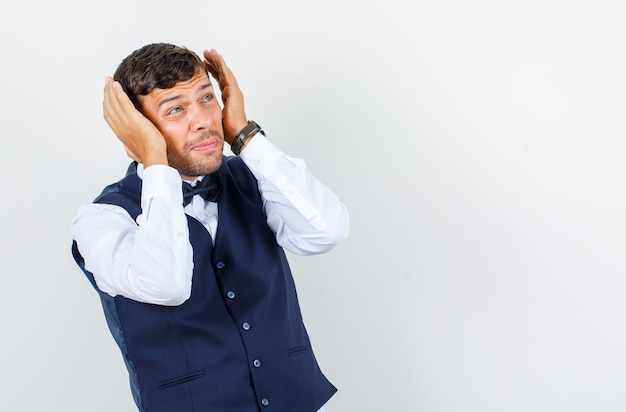 Kelner trzymający się za ręce w pobliżu głowy w koszuli, kamizelce i wyglądający na przestraszonego, widok z przodu.