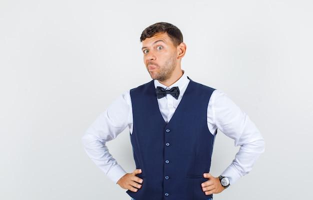 Kelner trzymający się za ręce w talii z założonymi ustami w koszuli, widok z przodu kamizelki.