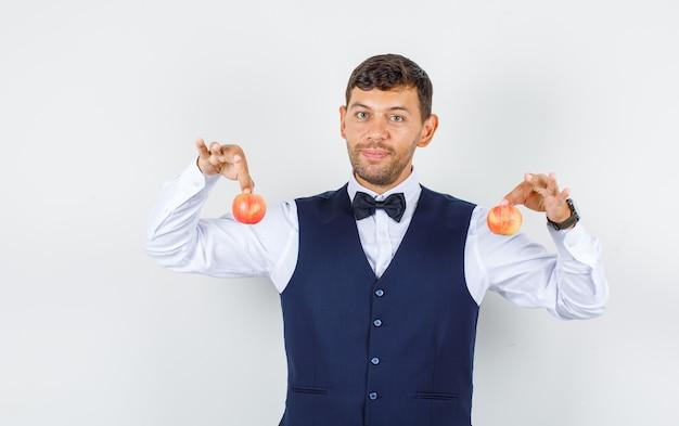 Kelner trzymający świeże jabłka w koszuli, kamizelce i wyglądający wesoło. przedni widok.