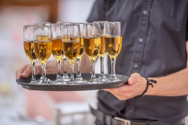 Kelner trzymający tacę pełną napojów w kieliszkach do szampana.