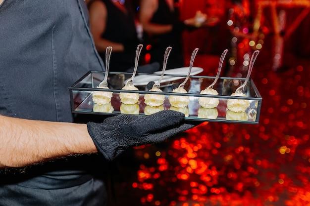 Kelner trzymający w rękach tacę z serową przystawką delikatne przekąski
