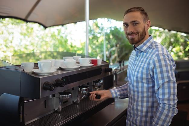 Kelner używa ubijaka do wciskania zmielonej kawy do kolby