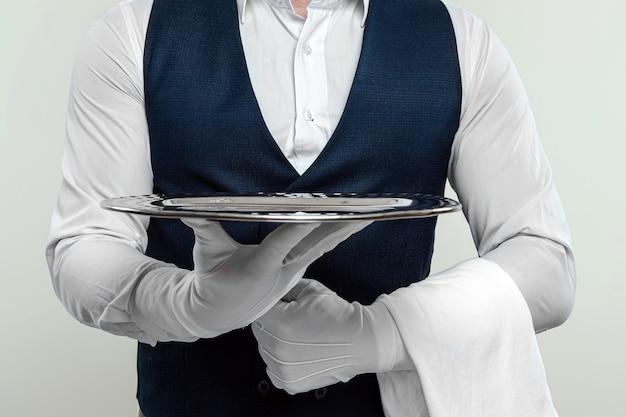 Kelner w białej koszuli i białych rękawiczkach stoi ze srebrną tacą. koncepcja obsługi obsługującej klientów w restauracji.