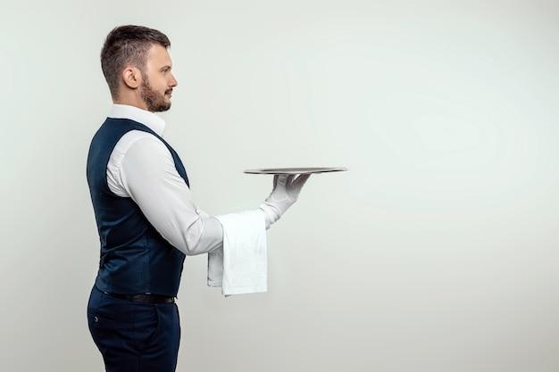 Kelner w białej koszuli stoi bokiem ze srebrną tacą. koncepcja obsługi obsługującej klientów w restauracji.