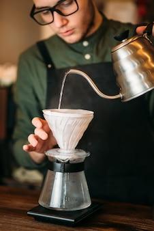 Kelner w czarnym fartuchu i okularach nalewa gorącą przegotowaną wodę do stojącego na blacie dzbanka do kawy.