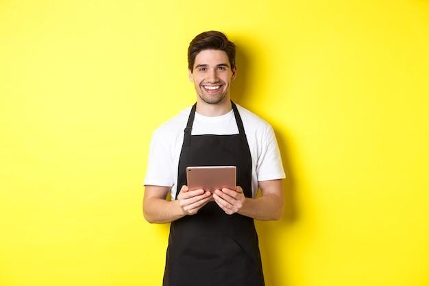 Kelner w czarnym fartuchu przyjmujący zamówienia, trzymający cyfrowy tablet i uśmiechnięty przyjaźnie, stojący na żółtym tle