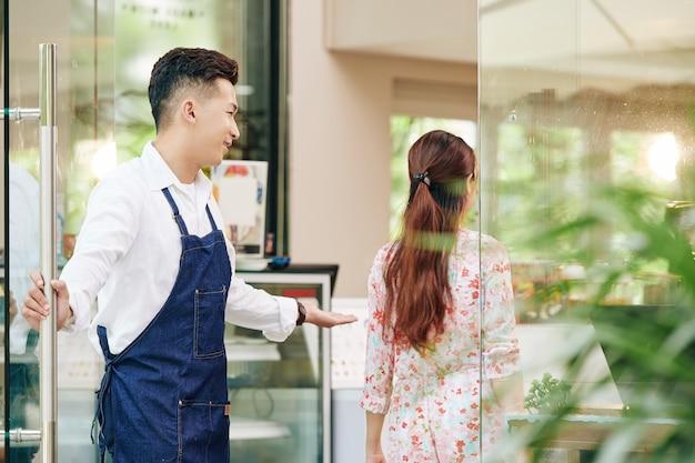 Kelner w kawiarni wita klienta