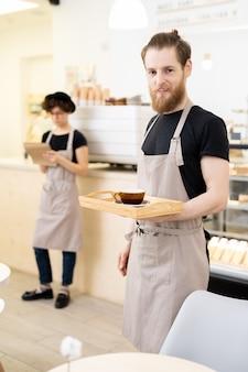 Kelner w kawiarni z tacą z filiżanką