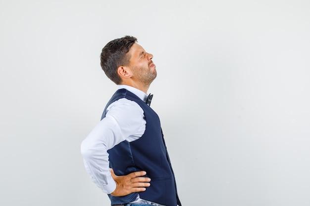 Kelner w koszuli, kamizelce, dżinsach cierpiący na ból pleców i wyglądający na chorego.