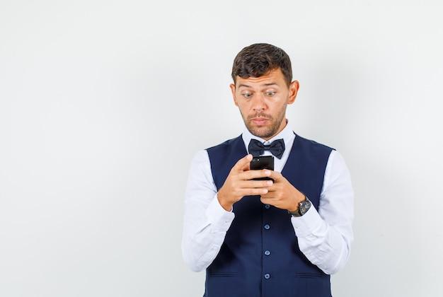 Kelner w koszuli, kamizelce, korzystający z telefonu komórkowego i wyglądający na podekscytowanego, widok z przodu.
