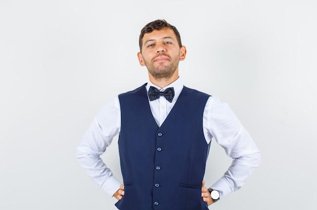 Kelner w koszuli, kamizelce stojącej z rękami w pasie i wyglądającej pewnie, widok z przodu.