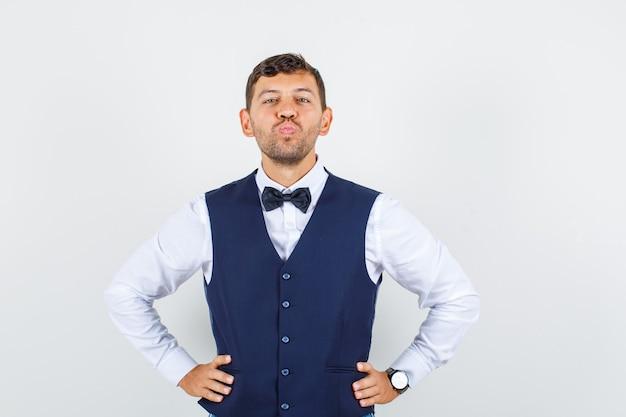 Kelner w koszuli, kamizelce trzymającej ręce w pasie z założonymi ustami, widok z przodu.